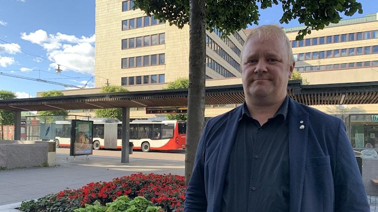 En man står framför en buss.