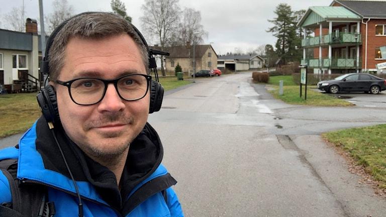 Håkan Eng med en gata och hus i bakgrunden.