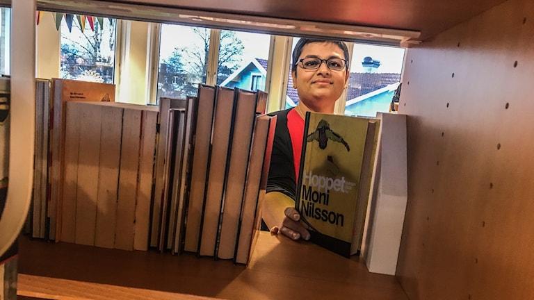 Shareen Fors syns genom en bokhylla. Hon håller en bok i handen.
