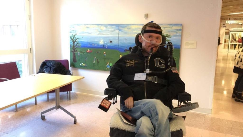 Sten Davidsson sitter i eldriven rullstol med andningshjälp i form av en batteridriven apparat.