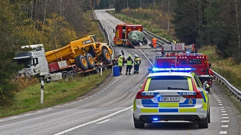 En lastbil vid sidan av vägen. Polisbil och räddningstjänst står också på vägen.