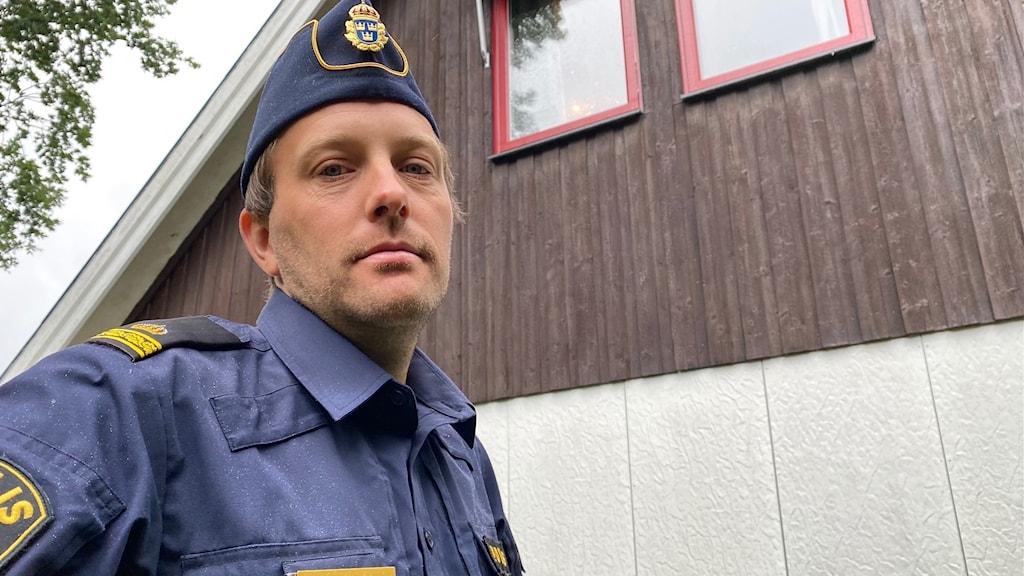 grodperspektiv på polisen Joakim Wallberg i blå polisskjorta och polisens mössa. Fönster på en villas övervåning i bakgrunden.