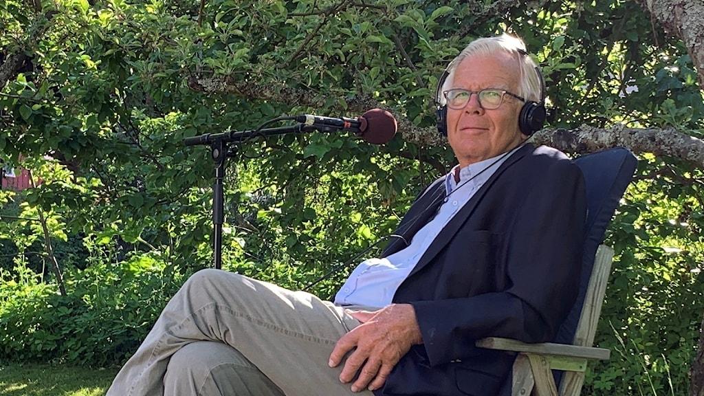 En man i kavaj sitter i en solig trädgård under ett träd