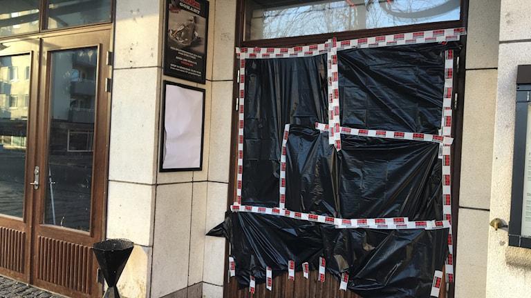 Dörren som besköts har täckts över med svart plast.