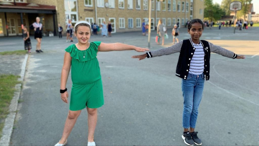 Antonia och Melat på Nyhemsskolan i Nässjö visar hur man håller avstånd genom att hålla ut armarna.