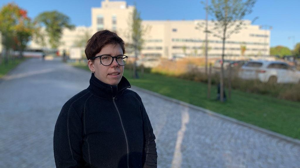 En kvinna i svarta kläder står framför en sjukhusbyggnad.