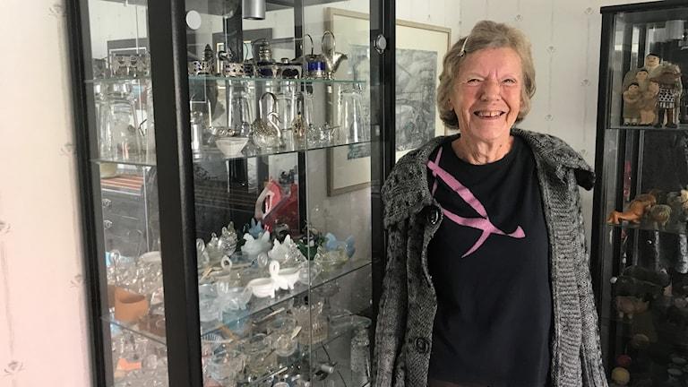 Lisbeth Öhlin Petersson står bredvid ett glasskåp fullt av saltkar av olika modeller.