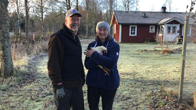 Anders och Lena står utanför sitt röda hus. Lena håller en höna i famnen.