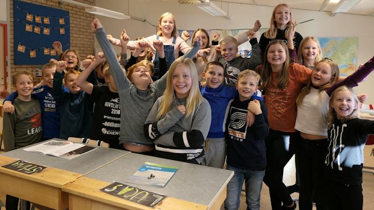 Barnen jublar i ett klassrum.