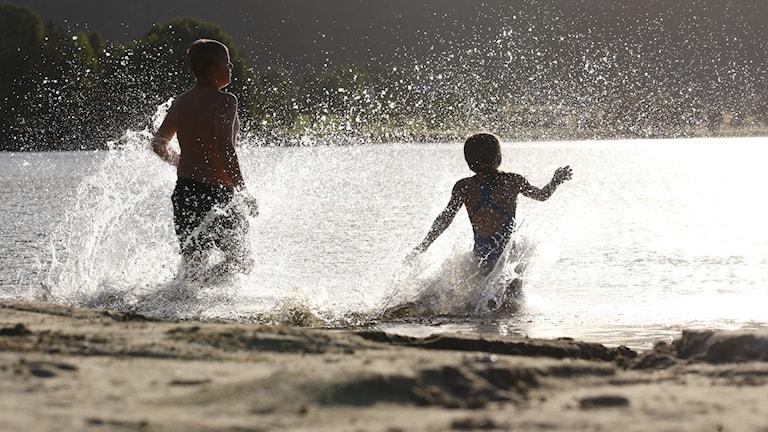Två barn springer ut i en sjö i kvällsljus.