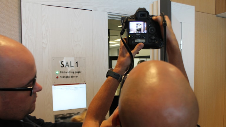 Personer fotograferar in i en rättssal.
