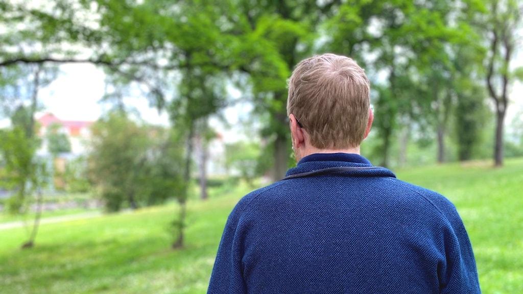 Anonym man står med ryggen mot kameran.