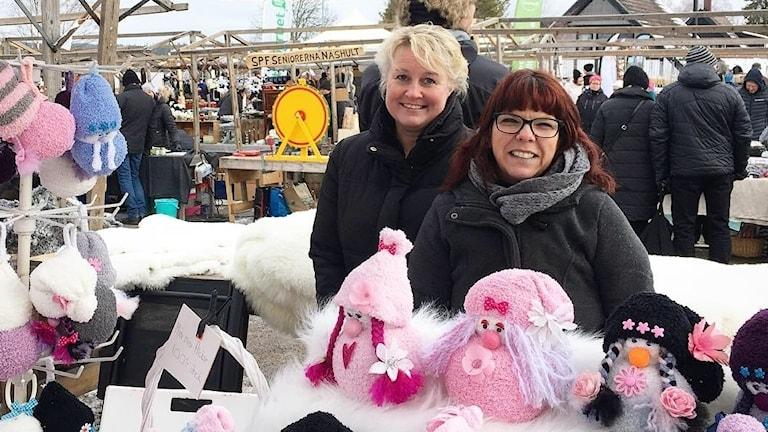 Två kvinnor i marknadsstånd bakom färgglada mjukdockor.