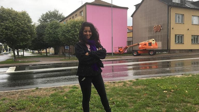 Saadia Hussein står med armarna i kors framför en rosa vägg.