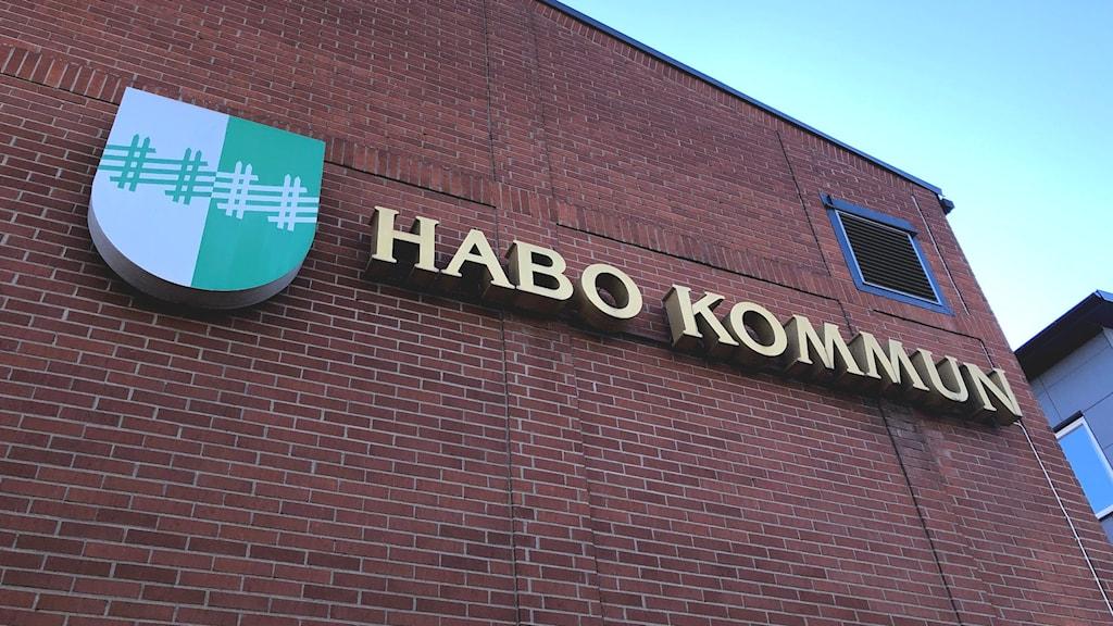 Habo kommun i guldiga bokstäver på tegelvägg.