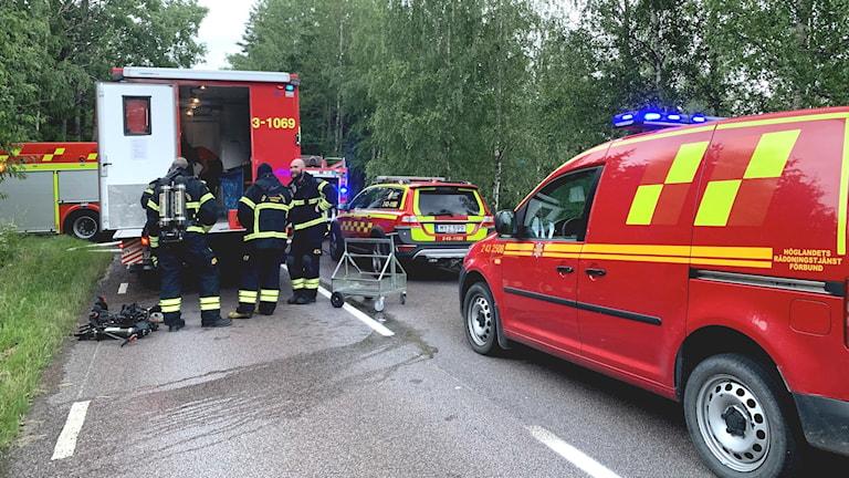 Brandmän står runt en brandbil som har blåljusen på.