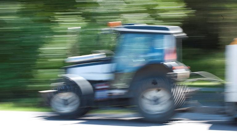 En suddig bild av en traktor som åker på en väg.