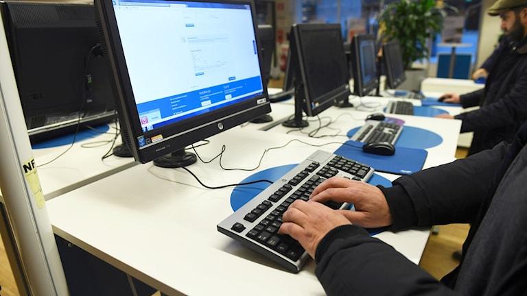 En person sitter vid en dator.