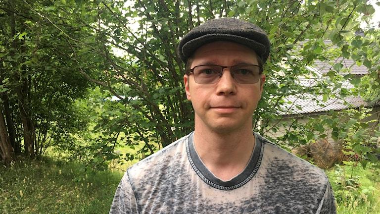 Man i glasögon iklädd grå t-shirt och med basker på huvudet står i grön utomhusmiljö.