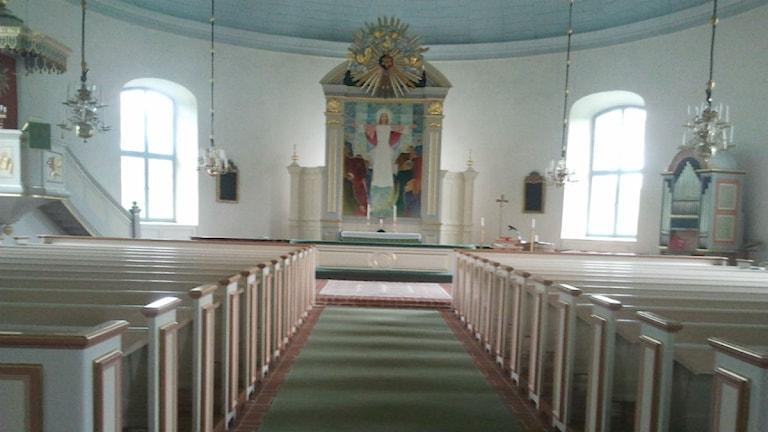 Kyrkbänkar och altaret i Rydaholms kyrka.