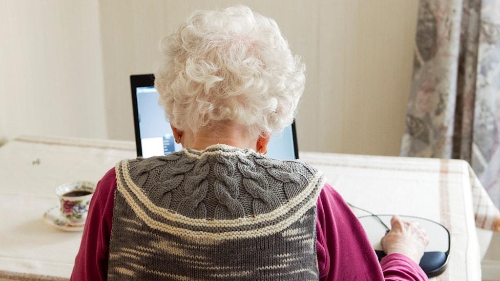 Äldre kvinna framför dator.