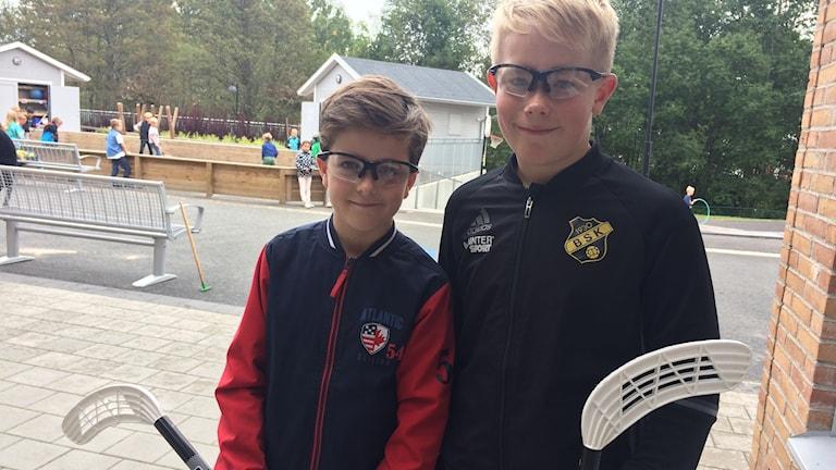 Eleverna Axel Geijer och Noel Hvitfeldt står med skyddsglasögon på sig och var sin innebandyklubba i handen.