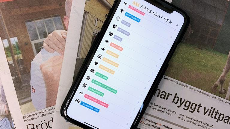 En mobiltelefon ligger på några papperstidningar.