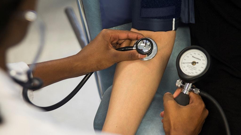 En läkare mäter blodtrycket på en patient.