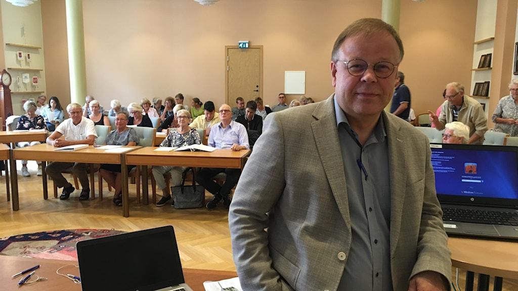 En manlig föreläsare framför åhörare.