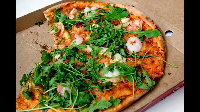 En pizza, med ruccolasallad på toppen, i pizzakartong.