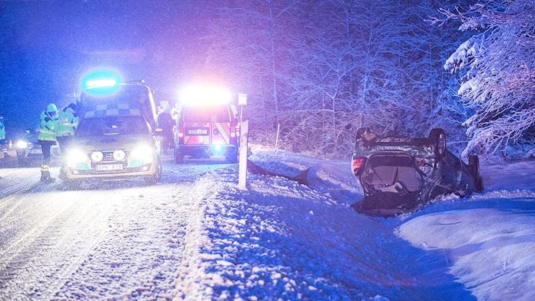 En bil ligger på taket vid sidan av en snöig väg. Ambulans och räddningstjänst står på vägen.