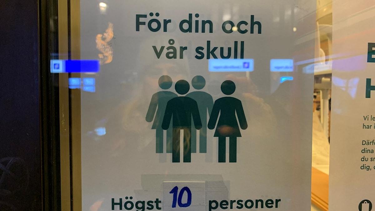 """En vit skylt på en glasdörr där det står """"För din och vår skull: Högst 10 personer i butiken samtidigt"""" med grön text."""