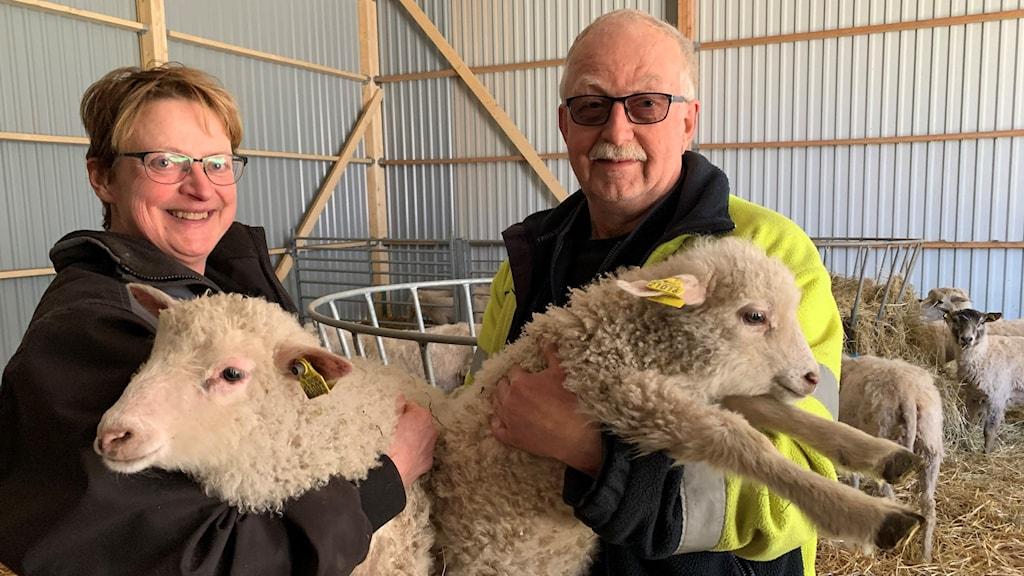 En kvinna och en man står och håller i varsitt vitt lamm.