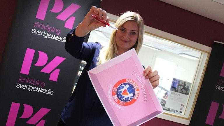 Therese Edin håller i en penna och ett papper med texten 25 000 kronor.