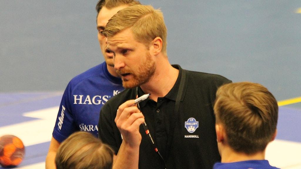 Hallbys tränare Jesper Östhlund lägger upp taktiken under en timeout.