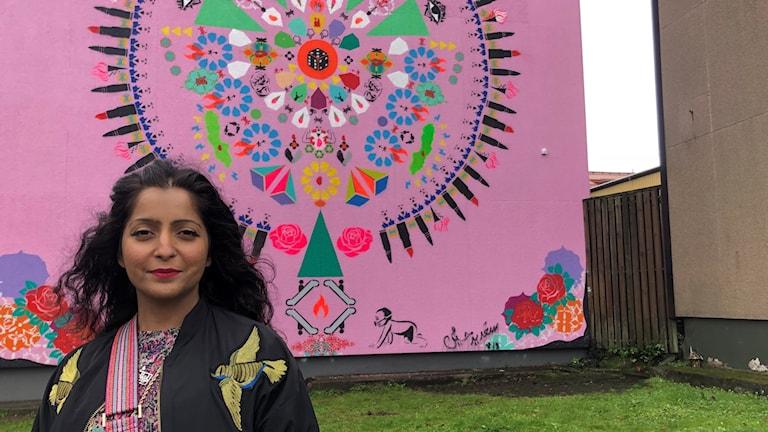 Saadia Hussain står framför en rosa vägg med massa färgglada symboler på.