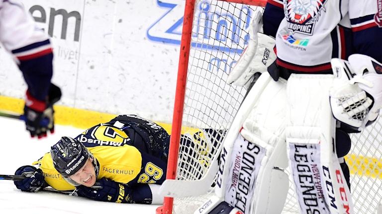 HV71-spelare ligger och grinar illa på isen bakom Linköpings målvakt.