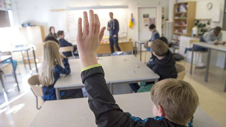 En elev räcker upp handen i ett klassrum.