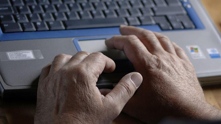 Ett par händer skriver på tangenterna sin bärbara dator.