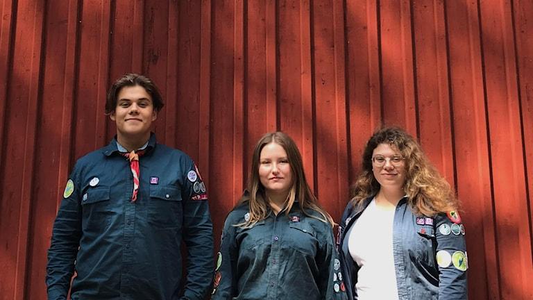Tre scouter i blå scoutskjortor framför en rödmålad träfasad.