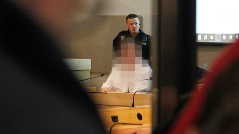 En man sitter i rättssalen. Bilden är blurrad.