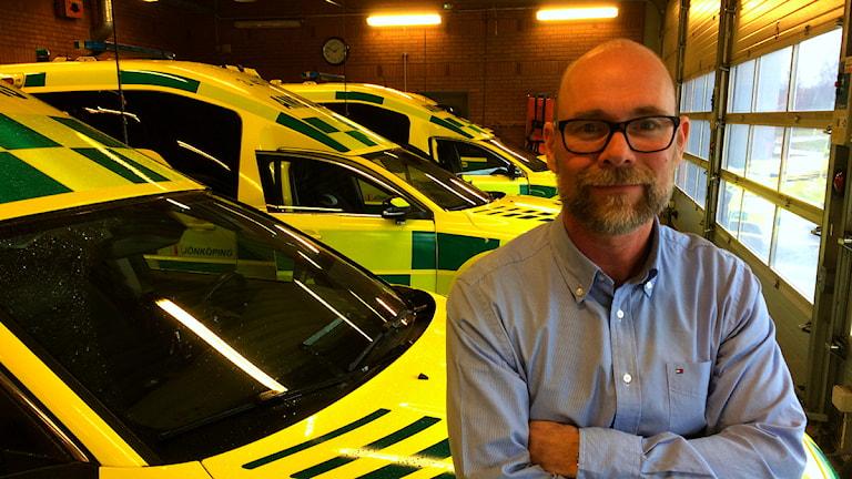 Daniel Lilja, chef över ambulanssjukvården, lutar sig mot en ambulans i ett garage.