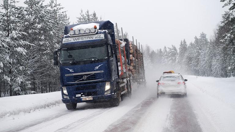 En lastbil och en personbil möts på en väg i yrande snö.