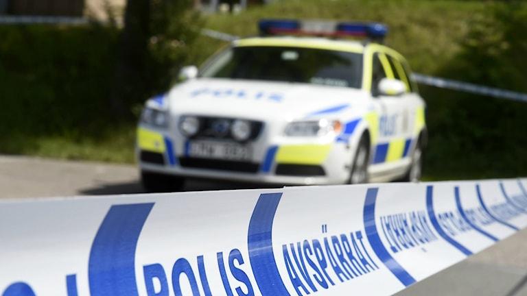 Polisbil och avstpärrningstejp.