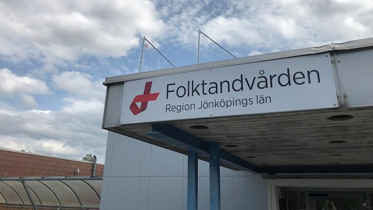 """Bilden visar skylten över entrén till Folktandvården i Vetlanda. Texten lyder: """"Folktandvården. Region Jönköpings län"""". Blå himmel i bakgrunden."""