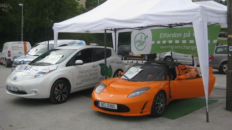 En lång rad elbilsmodeller visas upp under politikerveckan i Almedalen, här en modell från tillverkaren Tesla (orange) och en från Nissan. Foto: Peter Jernberg/Sveriges Radio