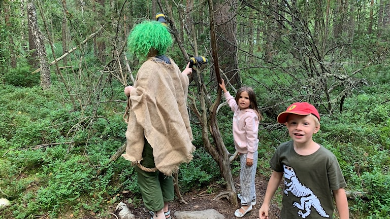 Troll med grön peruk och två små barn i skogen.
