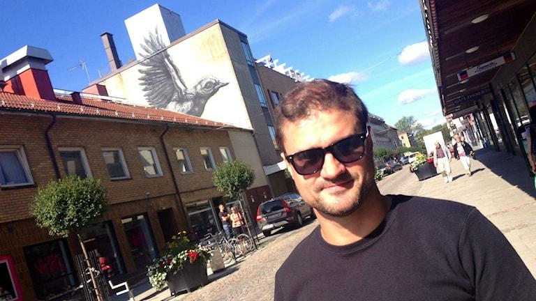 Lennart Alves är konsthallschef. Bakom honom syns väggmålningen som är gjord av ROA, en känd streetart-konstnär. Foto: Kajsa Hallberg/Sveriges Radio