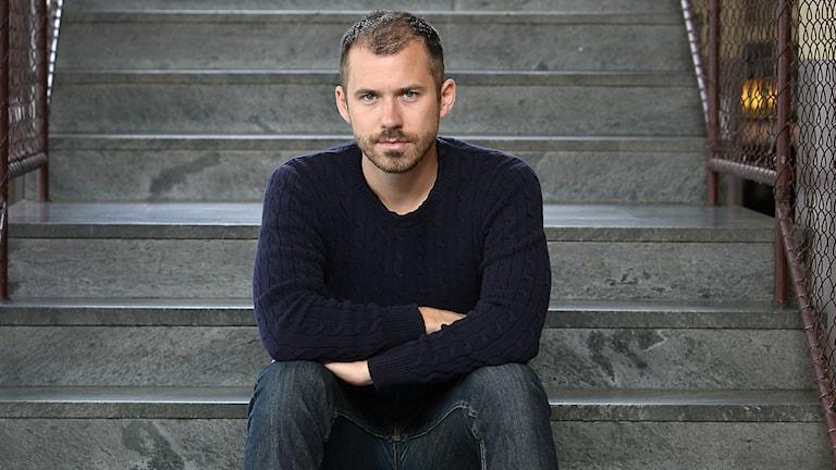 Expos chefredaktör Daniel Poohl sitter i en trappa med armarna i kors.