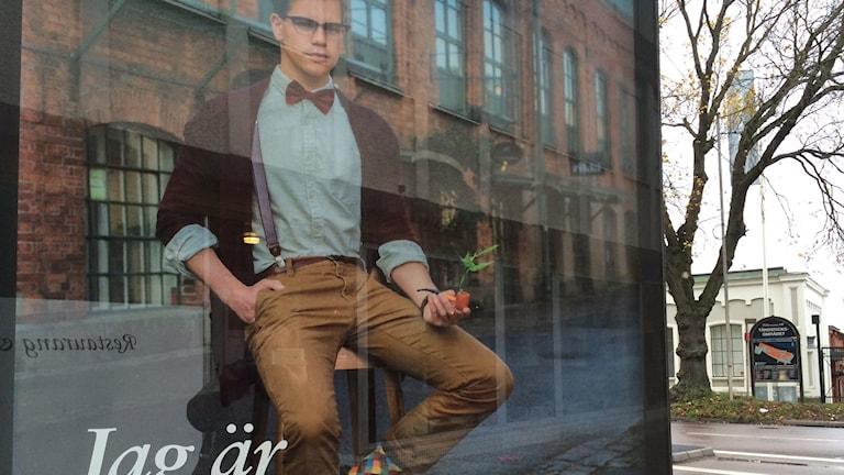 Bild på fotot där en ung man sitter med en pipa och ett grönt blad sticker upp ur den. Foto: Maria Rymell/Sveriges Radio